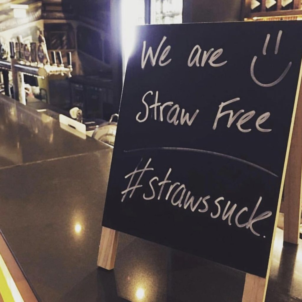 small blackboard on a bar with words we are straw free #strawssuck