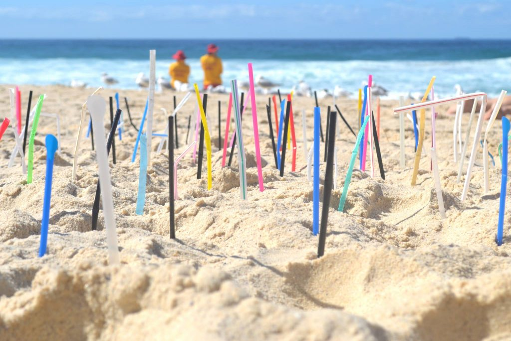 Beach with straws sticking upright in the sand and 2 life guards in the background